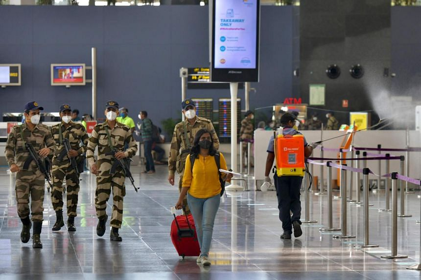 An airport worker sprays disinfectant at the domestic departure check-in terminal of Bangalore International Airport, on June 2, 2020.