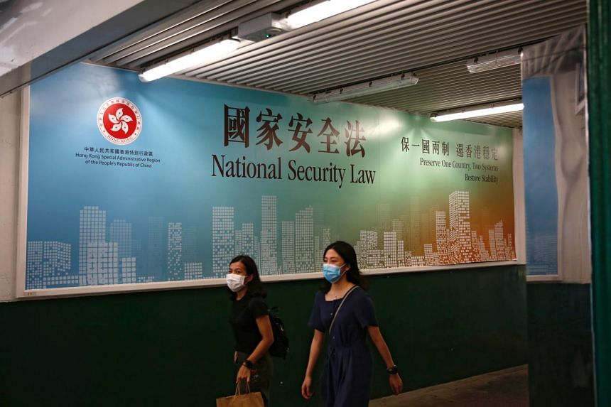 Women walk past an advertisement promoting the new national security law in Hong Kong, on June 29, 2020.