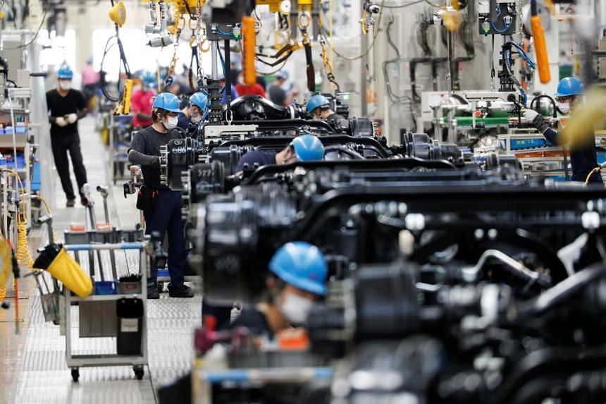 Employees work on the automobile assembly line at the Kawasaki factory of Mitsubishi Fuso Truck and Bus Corp, on May 18, 2020.