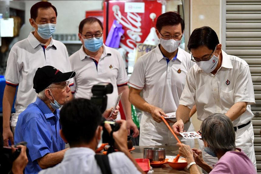 Deputy Prime Minister Heng Swee Keat (right) and MP Lee Yi Shyan (second from right) during a walkabout at Bedok Interchange Hawker Centre on June 30, 2020.