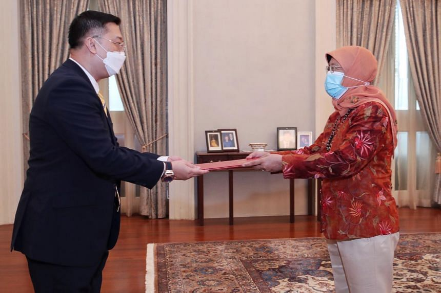 President Halimah Yacob (right) presenting the letter of credence to Singapore's High Commissioner-designate to the Republic of India Simon Wong.