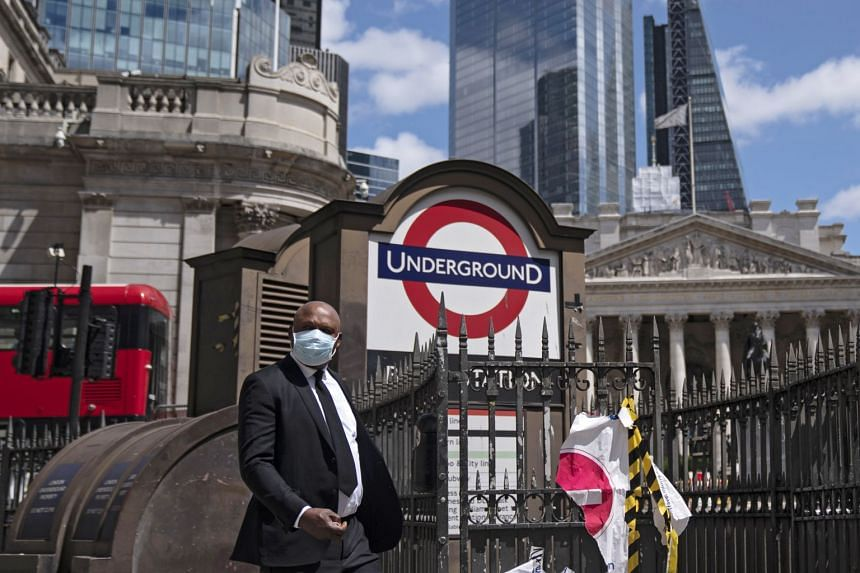 A member of the public passes through the City of London financial centre, June 29, 2020.