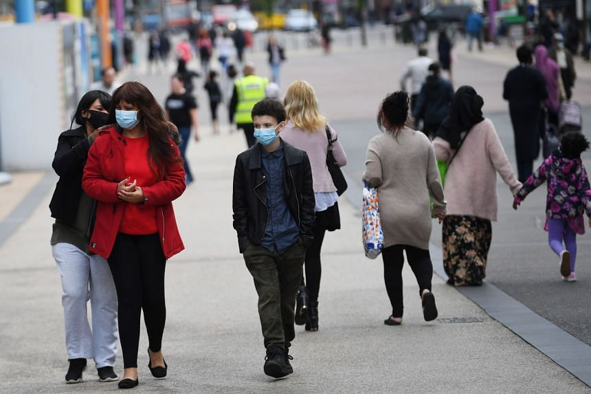 People wear face masks as they shop in Leicester city centre, June 30, 2020.