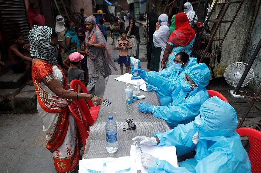 A healthcare worker checking the temperature of a woman in Mumbai yesterday, during a medical campaign to curb the spread of Covid-19. PHOTO: REUTERS