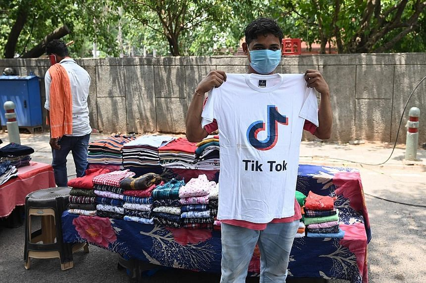 A garment vendor in New Delhi holding up a TikTok T-shirt yesterday. Of the Chinese apps India has banned, TikTok is the most popular, with about 200 million active users in the country. The move could affect how millions of Indians work and play.