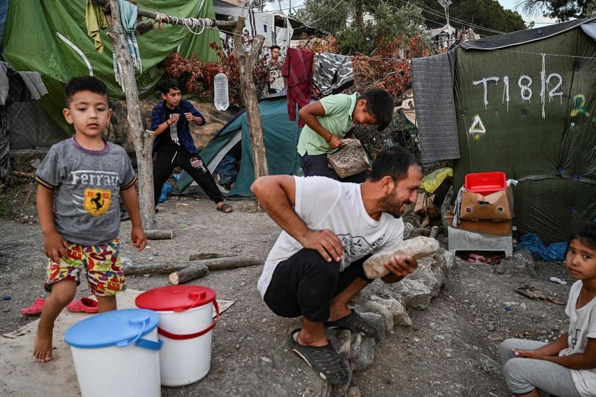 Migrants are pictured in an improvised camp near the refugee camp of Moria on the island of Lesbos on June 21, 2020.