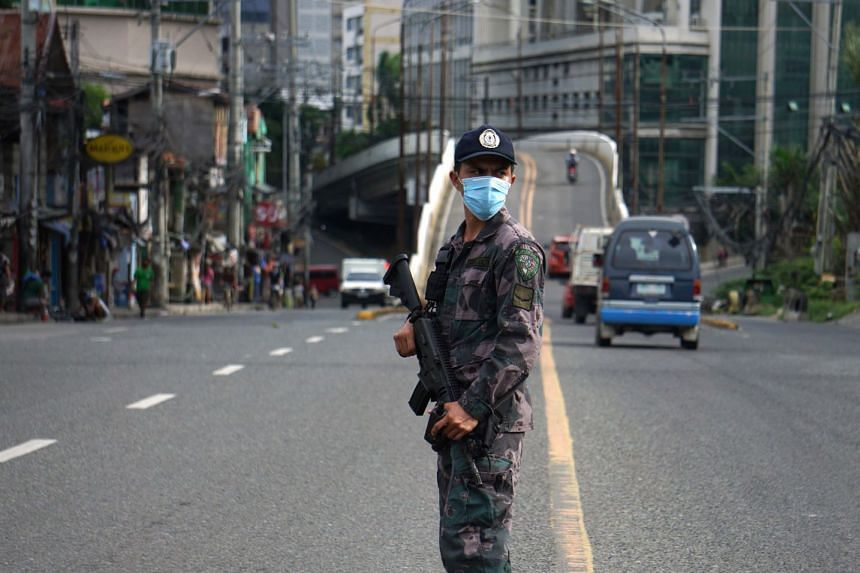 A police officer mans a checkpoint along a road in Cebu City, central Philippines on June 24, 2020.