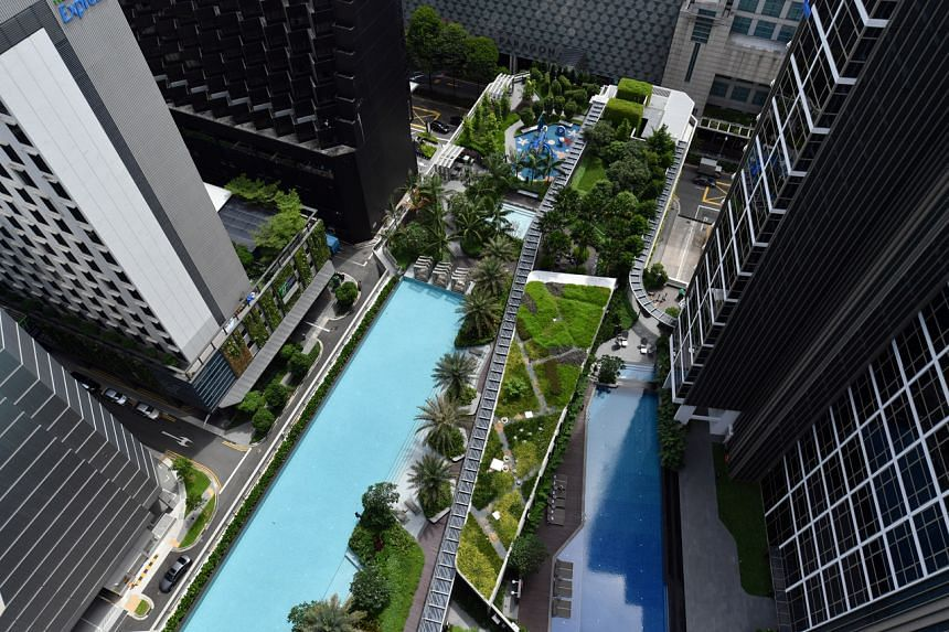 A condominum which has a green hanging garden with potted plants.