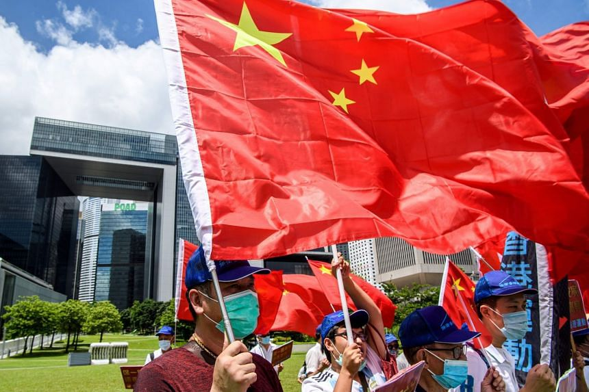 Pro-China supporters display Chinese and Hong Kong flags during a rally on June 30, 2020.