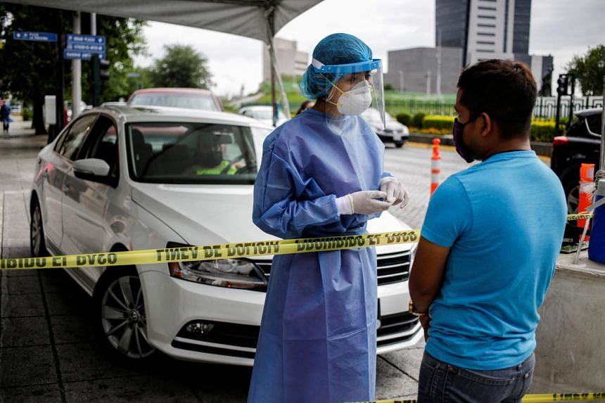 A healthcare worker talks to a man before collecting a swab sample at a drive-thru testing site in Monterrey, Mexico, on June 26, 2020.