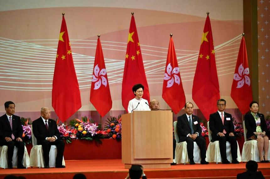 Chief Executive Carrie Lam (centre) speaks to guests after a flag-raising ceremony to mark the 23rd anniversary of Hong Kong's handover from Britain, on July 1, 2020.