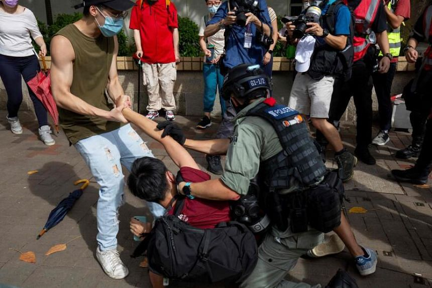 A police officer tries to detain a man during a rally against a new national security law in Hong Kong, on July 1, 2020.