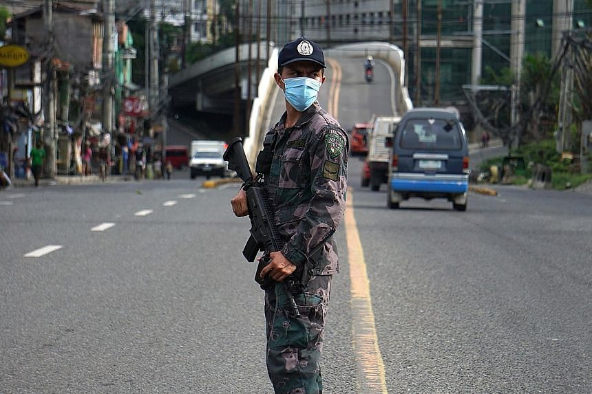 A police officer in Cebu City last week, manning one of about 100 checkpoints around the city to enforce a strict lockdown meant to contain the Covid-19 outbreak there.