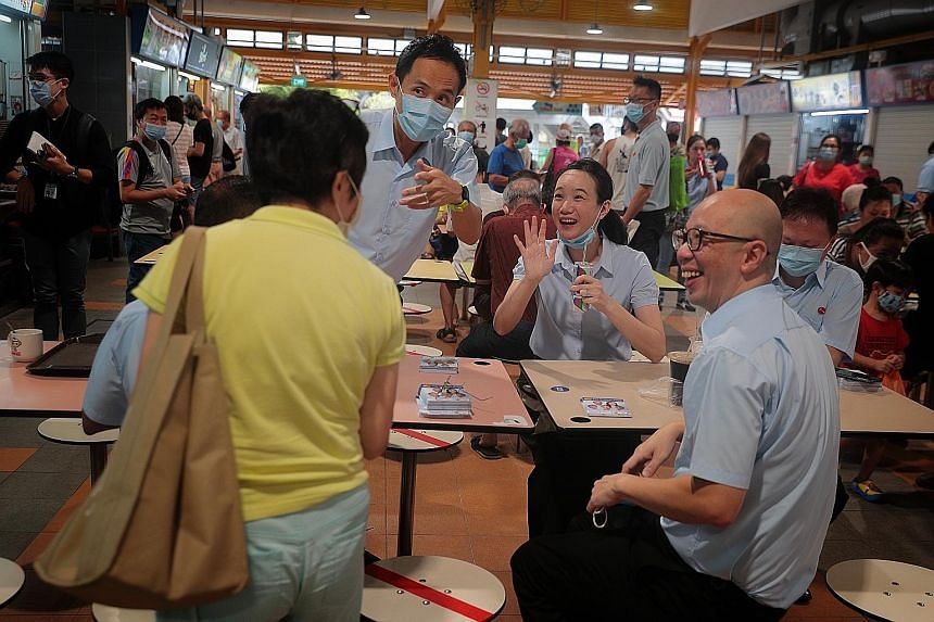 Workers' Party candidates for East Coast GRC (from left) Abdul Shariff Aboo Kassim (obscured), Kenneth Foo, Nicole Seah, Terence Tan and Dylan Ng greeting a well-wisher during a walkabout in Bedok yesterday.