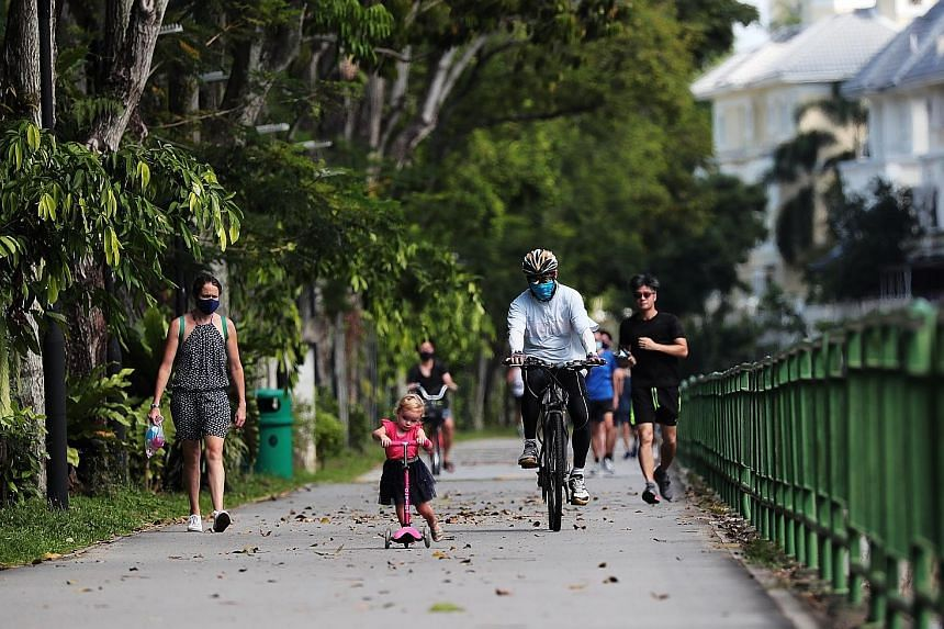 A cyclist breezing through the path of the Ulu Pandan Park Connector while sharing it with a girl on her kick scooter in May, while Singapore was in the circuit breaker to halt the transmission of the coronavirus.