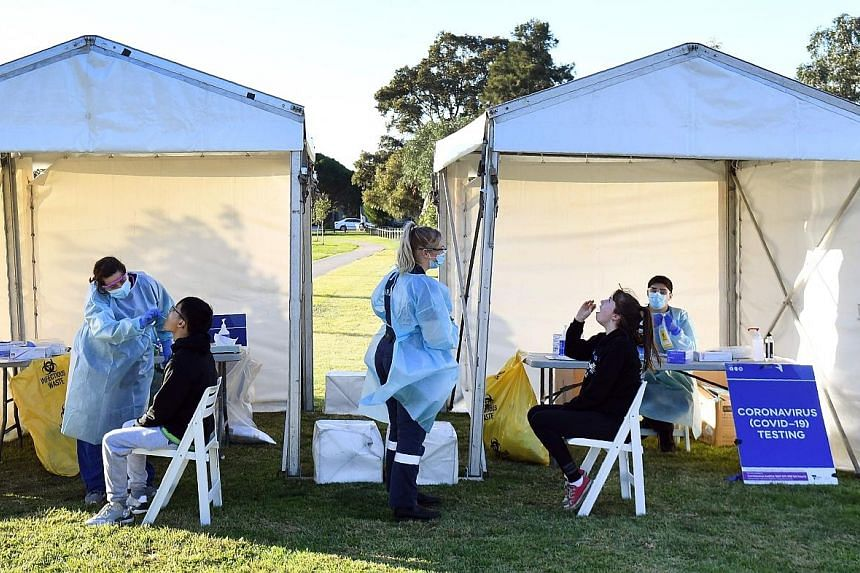 People having their swab samples taken to be tested for the coronavirus in a suburban park in Melbourne yesterday. PHOTO: AGENCE FRANCE-PRESSE