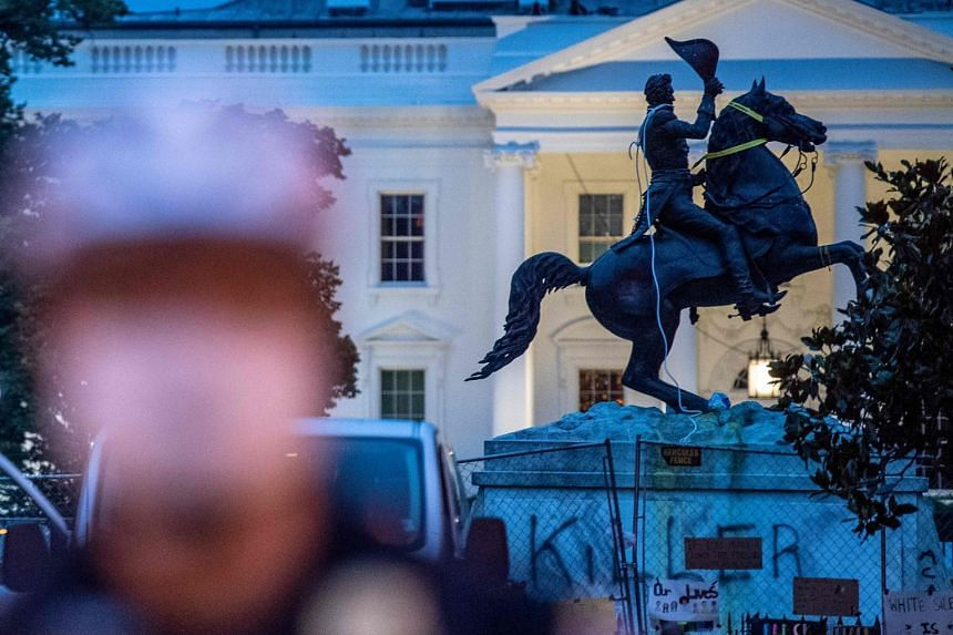 A defaced statue of former US president Andrew Jackson has ropes and chains still hanging on it after protesters tried to topple it, at Lafayette square, in front of the White House.
