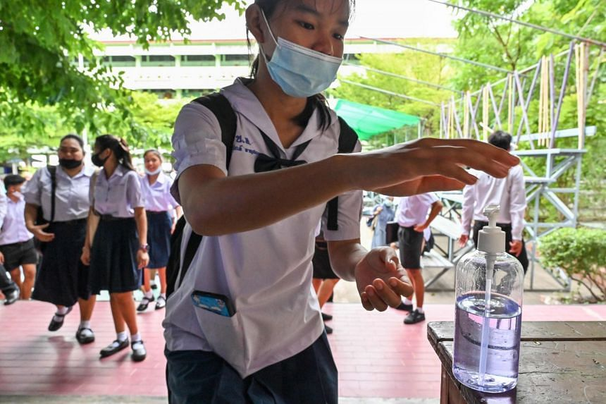 A student uses hand sanitiser as she arrives at a secondary school in Bangkok on July 1, 2020.
