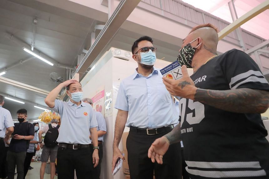 Workers' Party chief Pritam Singh (centre) talking to a resident during a walkabout at Kovan Hougang Market and Food Centre on July 2. With him is former party chief Low Thia Khiang.