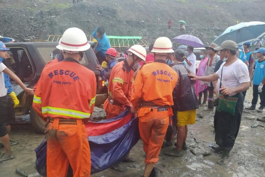 Rescue workers carry a body following a landslide at a mining site in Phakant, Myanmar, on July 2, 2020.