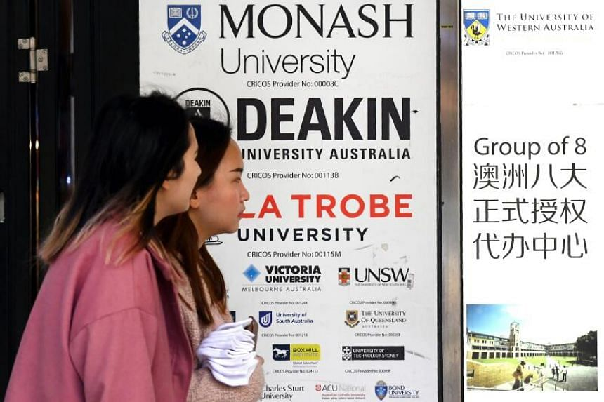 People walk past a sign for Australian universities in Melbourne's central business district, on June 10, 2020.