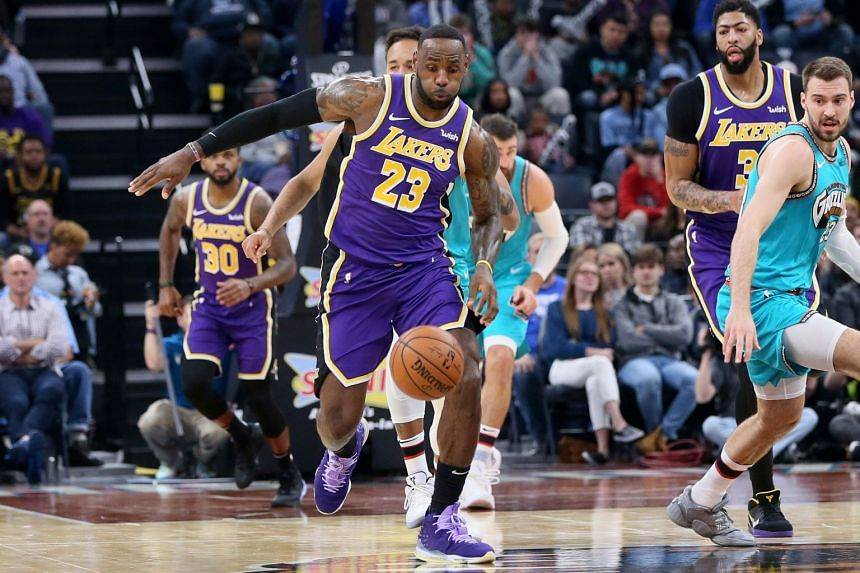 Lakers forward LeBron James (23) reaches for a loose ball as Memphis Grizzlies guard Marko Guduric (23) and Lakers forward Anthony Davis (3) look on in November 2019.