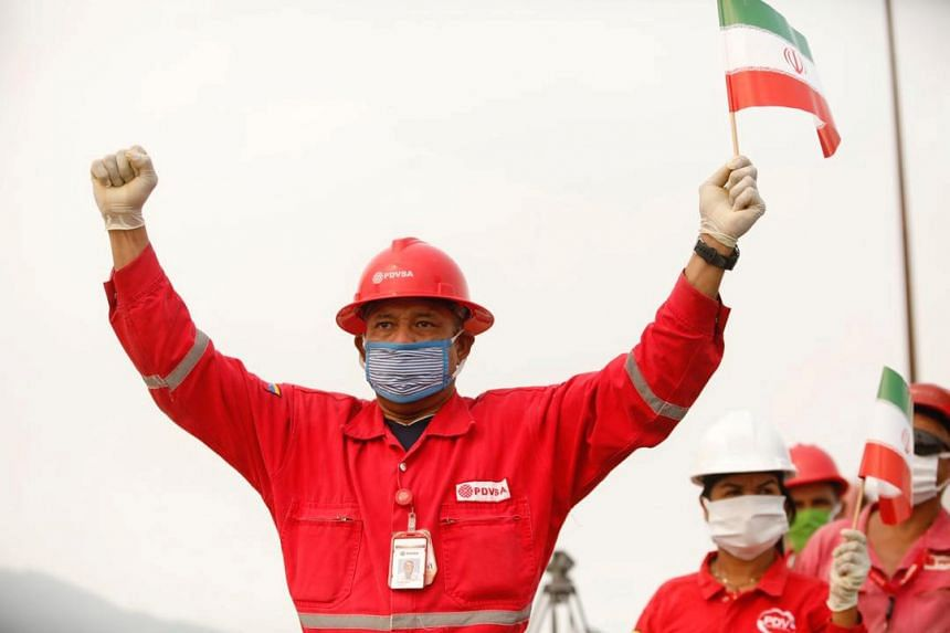 "A worker of the state-oil company Pdvsa holds an Iranian flag during the arrival of the Iranian tanker ""Fortune"" at El Palito refinery in Puerto Cabello, Venezuela in May 2020.."