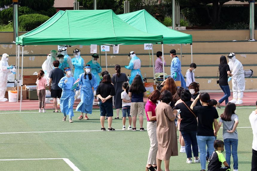 Students, their parents and teachers of Cheondong Elementary School lining up in Daejeon, South Korea, on July 2, 2020.