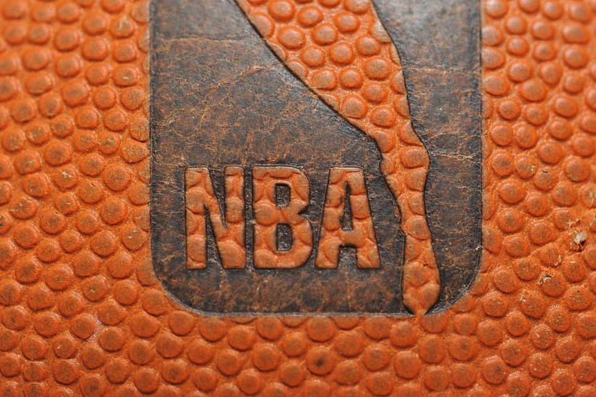 A file photo shows the NBA logo on a basketball.