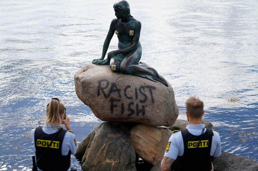 View of the 'Little Mermaid' statue with the message 'Racist Fish' on it in Copenhagen, Denmark, on July 3, 2020.