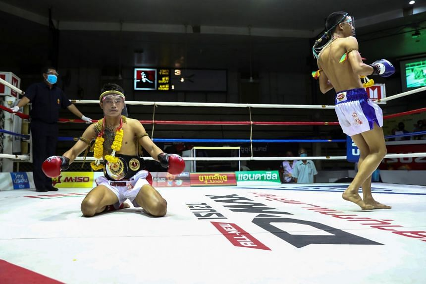 Muay Thai boxers wearing face shields perform the Muay Thai traditional dance before their fight in front of empty spectator seats.