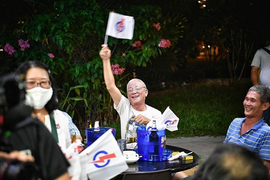 A boy gets a party flag from PAP East Coast GRC candidate Maliki Osman during a walkabout in Simei. WP team members (from left) Nicole Seah, Terence Tan and Abdul Shariff Aboo Kassim at Bedok Central yesterday. A resident waving a People's Action Par