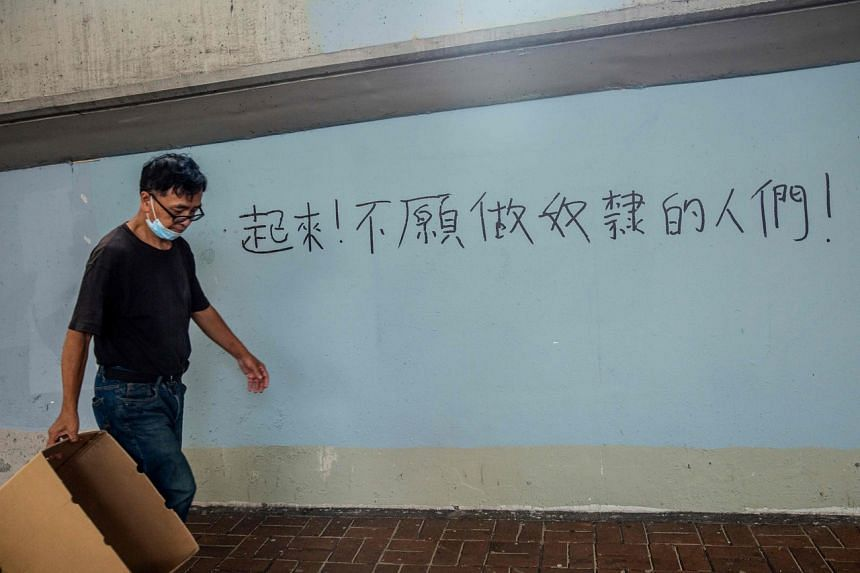 """A man walks past graffiti of a line from the Chinese national anthem, reading """"Arise, ye who refuse to be slaves"""", in Hong Kong on July 3, 2020."""