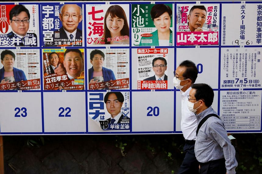 A wall of posters featuring candidates in Tokyo's election tomorrow. Governor Yuriko Koike (top row, in green blazer) is tipped to be re-elected, having won praise for her decisive handling of the Covid-19 outbreak. PHOTO: REUTERS