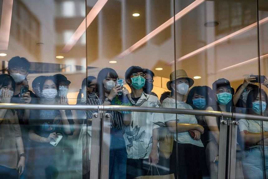 Bystanders watch protesters on a street below a shop during a rally against China's new law in Hong Kong on July 1, 2020.