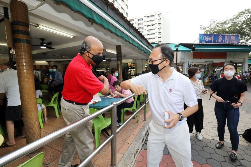 Singapore Democratic Party chairman Paul Tambyah and PAP Bukit Panjang SMC candidate Liang Eng Hwa greet each other while meeting residents in Bangkit Road on July 1, 2020.