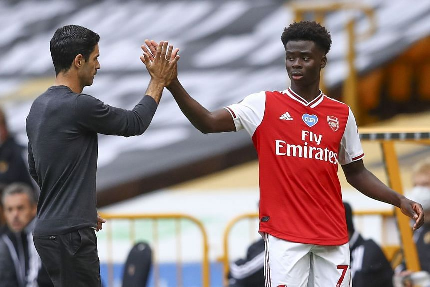 Arsenal's Bukayo Saka reacts after being substituted, with team manager Mikel Arteta.