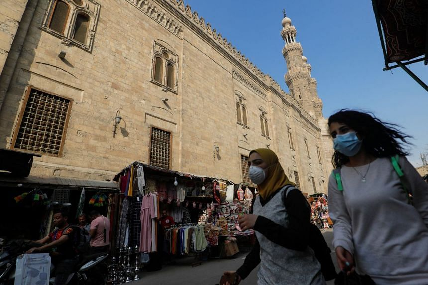 Women walk near Bab Zuweila, one of the surviving main gates of the old city of the Egyptian capital Cairo, in April 2020.