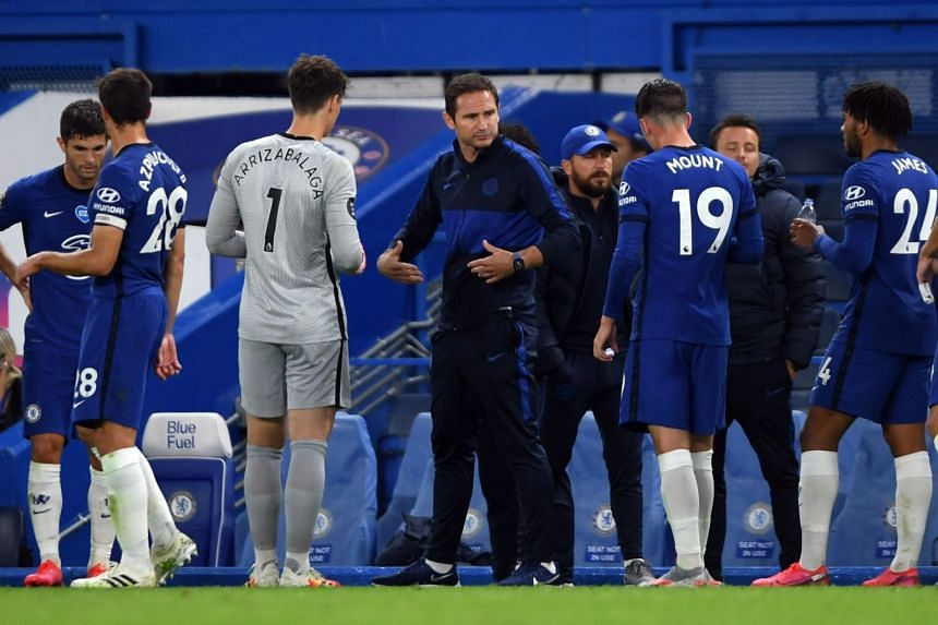 Chelsea manager Frank Lampard speaks with players during a drink break.