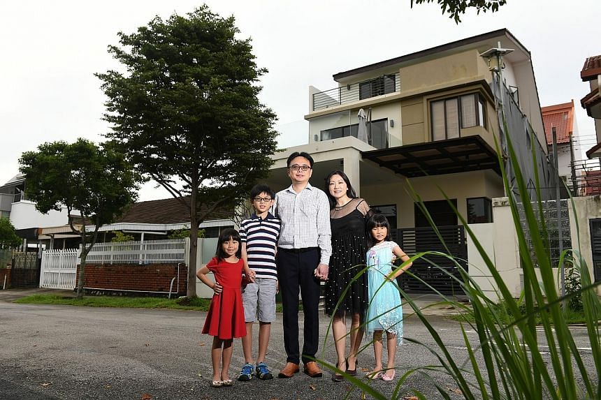 Ms Li and her family with their house in the background. The previous owner had planted a huge tree in front that blocks out the heat and provides shelter.