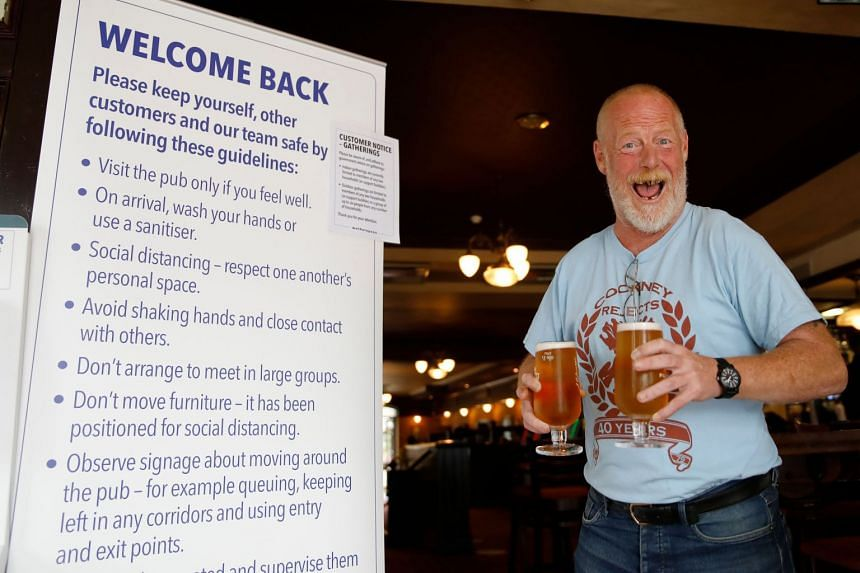 A customer reacts as he walks with two pints of beer at a London pub.