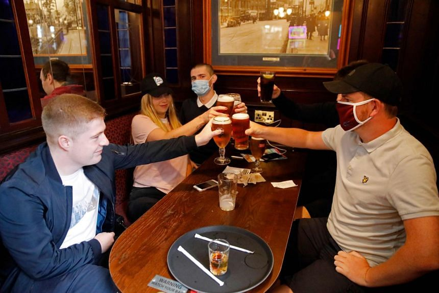 People make a toast at a Wetherspoon pub in London on July 4, 2020.