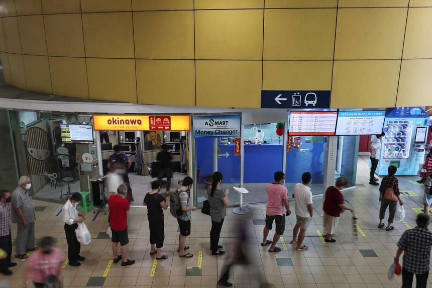 People queue to collect reusable masks at mask vending machines at the Toa Payoh bus interchange.