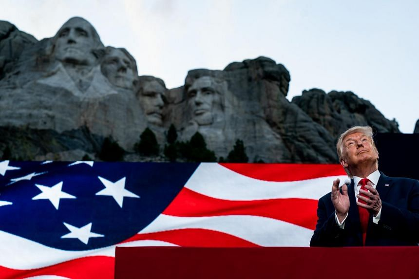 US President Donald Trump watches a military plane flyover at Mount Rushmore, on July 3, 2020.