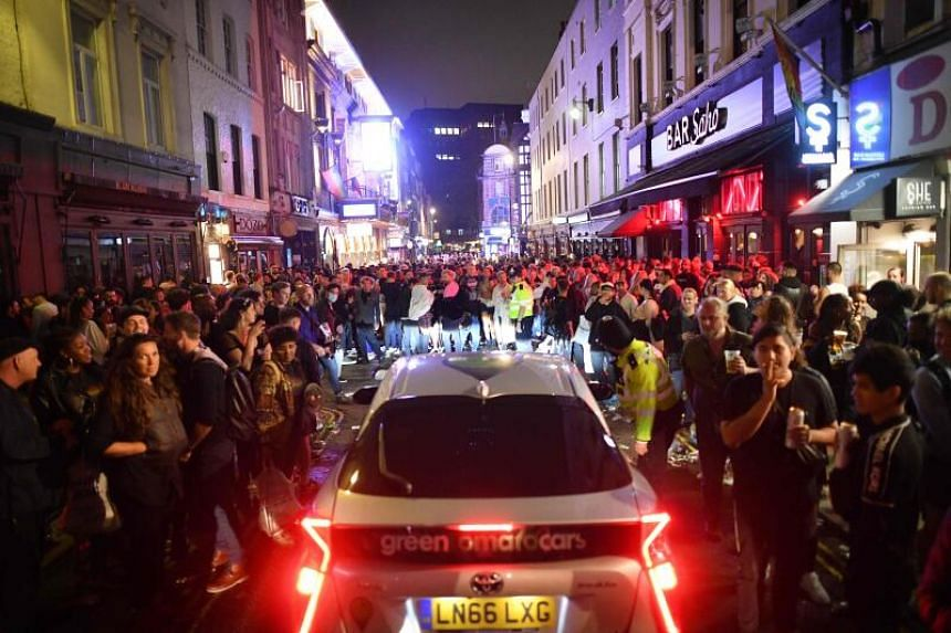 A car tries to drive along a street filled with people drinking in the Soho area of London, on July 4, 2020.