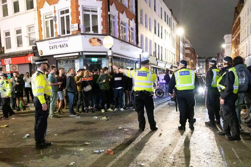 Police officers direct traffic as people drink and socialise in the street in Soho, London, on July 4, 2020.