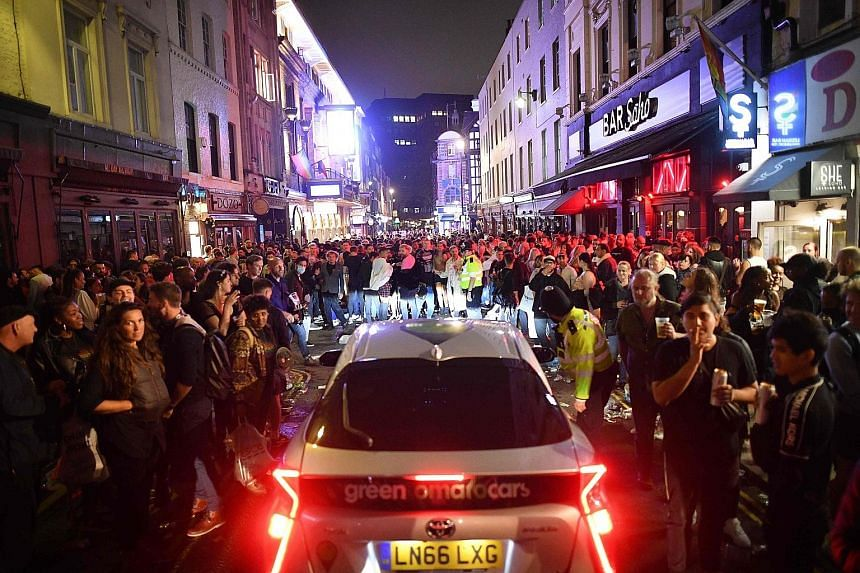 Revellers gathering in London's Soho area on Saturday, after pubs in England reopened that day for the first time since late March. Experts in Singapore say safe distancing and hygiene measures already in place here are generally sufficient to keep t