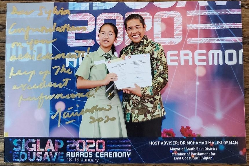Secondary 1 student Sylvia Low receiving the Edusave Merit Bursary and Edusave Good Progress Award in January from Dr Maliki Osman, Mayor of South East District. Dr Maliki linked her up with families who needed help. PHOTO: JEFF LOW