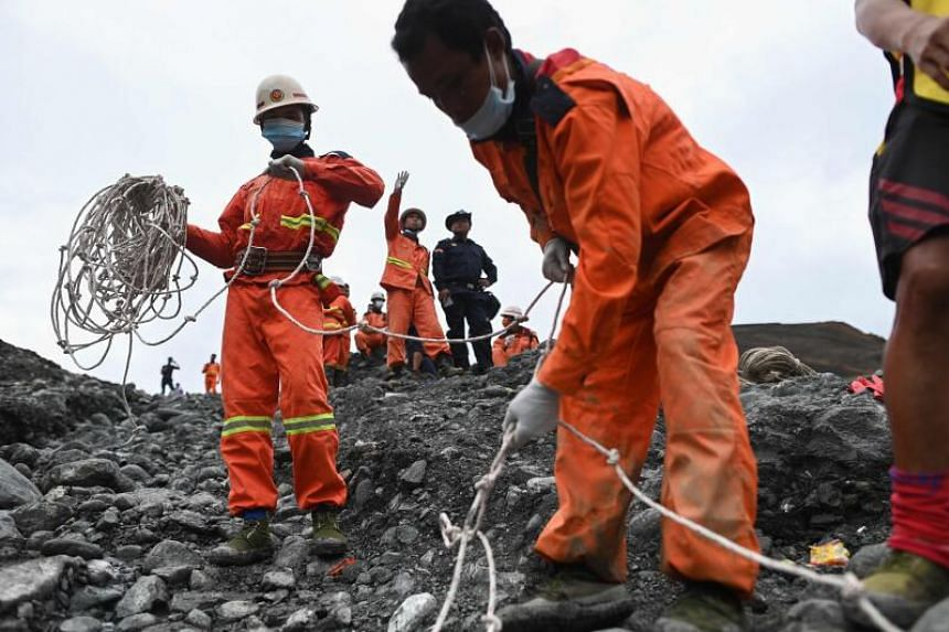 Rescue workers search for bodies at the site of a landslide near Hpakant in Myanmar's Kachin state on July 4, 2020.