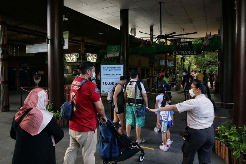 A staff member ensuring safe distancing between visitors at the entrance of the Singapore Zoo on July 6, 2020.